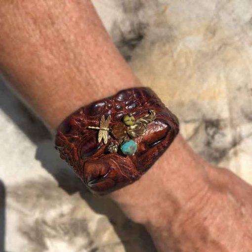 Model wearing crocodile Cuff bracelet with brass dragonfly glas bead